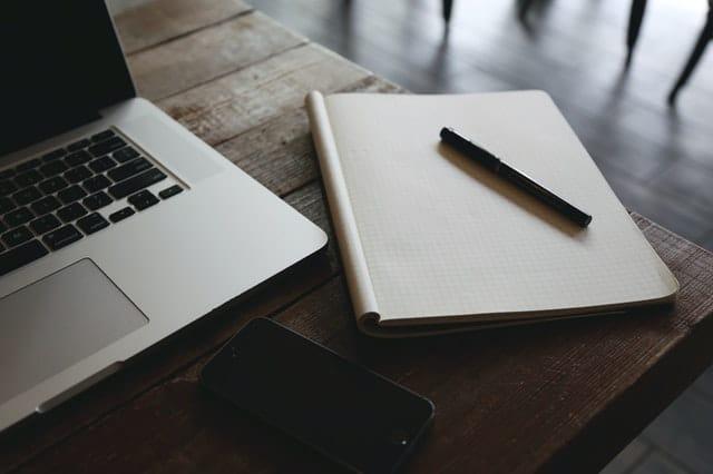 Un bureau avec un ordinateur portable et un cahier