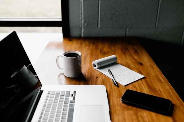 Un bureau avec un ordinateur portable et un café