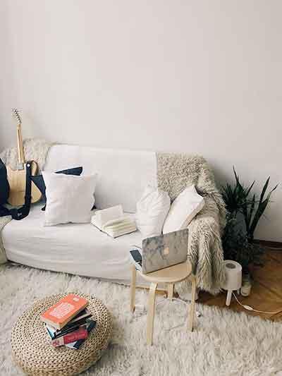 Un canapé confortable et cosy dans un pièce avec un ordinateur portable