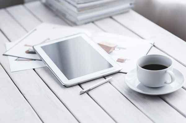 Un bureau avec une tablette et une tasse de café