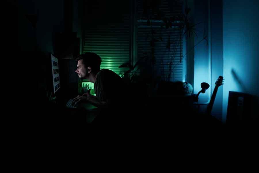 une homme devant son ordi dans le noir